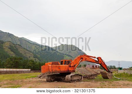 Large Orange Excavator With A Lowered Bucket During Repair Work In The Mountains On A Summer Day.