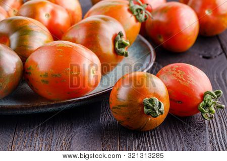 Fresh Whole Cherry Tomatoes And Slices Scattered On A Black Board