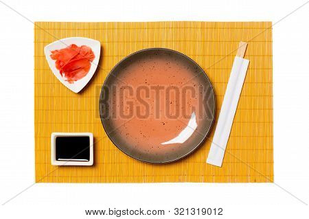 Empty Round Brown Plate With Chopsticks For Sushi, Ginger And Soy Sauce On Yellow Bamboo Mat Backgro
