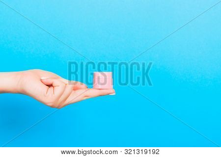 Female Hand Holding Cream Bottle Of Lotion Isolated. Girl Give Jar Cosmetic Products On Blue Backgro