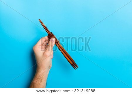 Crop Image Of Male Hand Holding Chopsticks On Blue Background. Japanese Food Concept With Copy Space