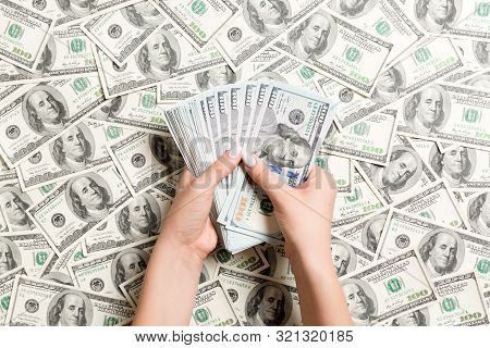 Top View Of Female Hands Counting Money On Dollar Background. Debt Concept. Investment Concept