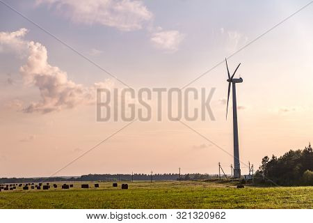 Rotating Blades Of A Windmill Propeller On Blue Sky Background. Wind Power Generation. Pure Green En