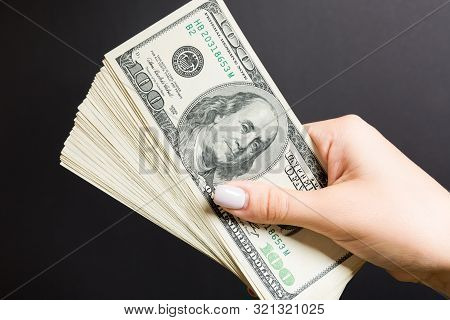 Top View Of Female Hand Holding A Fan Of One Hundred Dollars On Colorful Background. Loan Concept. P