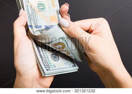 Top View Of Female Hands Counting Money. One Hundred Dollar Banknotes On Colorful Background. Salary