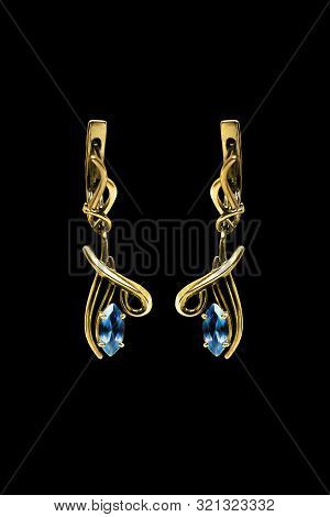 Pair Of Elegant Gold Earrings With Blue Gems On Black Background