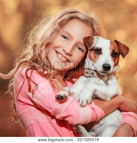 Child with dog at autumn. Happy girl with pet