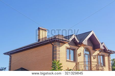 Modern Brick Chimney With Beautiful Forging Under Clear Blue Sky. Exterior Of Modern Brick House Wit
