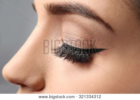 Young woman with elegant makeup and long eyelashes on grey background. Eyelash extensions