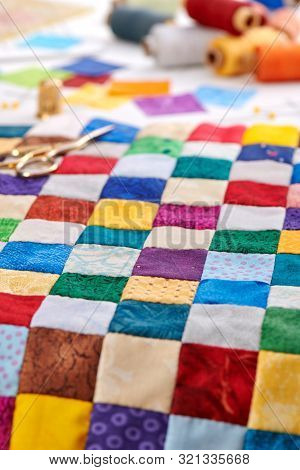 Colorful Part Of Quilt Sewn From Square Pieces, Spools Of Thread,  Quilting And Sewing Accessories