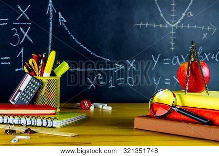 Mathematic Classroom At School. Math Formulas Drawn At Chalkboard. School Supplies: Physics Books, P
