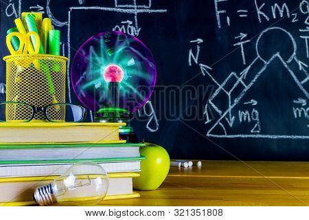 Physics Classroom At School. Physics Formulas Drawn At Chalkboard. School Supplies: Physics Books, P