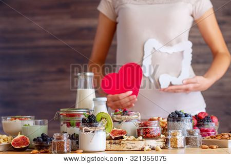 Female Hands Are Holding Capsules With Bifidobacteria In Left Hand And Natural Yogurt In Right. Youn