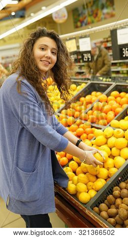 Young Woman Chooses Fruits In Grocer`s Shop, Touches To Lemons, Make Purchases In Supermarket, Eats