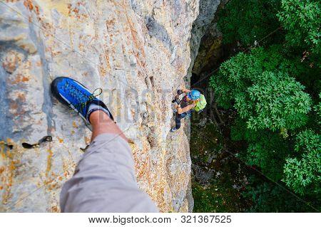 Woman Tourist Climbing A Vertical, Difficult Via Ferrata Section In Baia De Fier, Romania, On A Rout