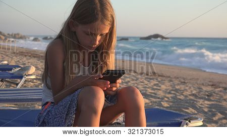 Child Playing Smartphone, Kid On Beach At Sunset, Girl Using Tablet On Seashore