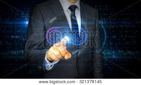 A Businessman In A Suit Touch Screen With Game Pad Symbol Hologram. Man Using Hand On Virtual Displa