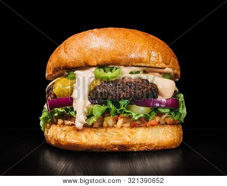 Craft Burger Is Cooking On Black Background. Consist: Sauce Salsa, Lettuce, Red Onion, Pickle, Chees