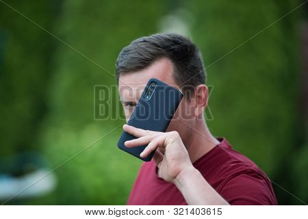 A Man Holds A Phone In A Protective Case. Phone Safety From Falling. Bumper On The Phone. Dark Phone