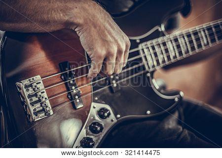 A Man Plays A Bass Guitar Close-up. Toned Photo.