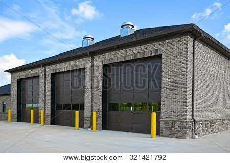 An New Brick Commercial Building With Three Large Garage Doors