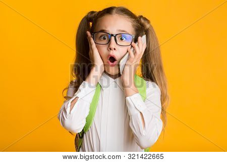 Oops, Bad News. Surprised Schoolgirl Holding Smartphone To Ear Over Yellow Background. Free Space, S