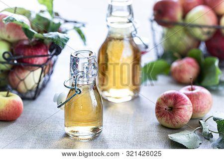 Apple Vinegar. Bottle Of Apple Organic Vinegar Or Cider On Wooden Background. Healthy Organic Food.