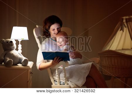 Mother Reading A Book To Little Baby