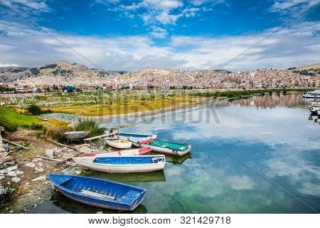 Boats and panoramic view on Puno from Titicaca lake, Peru