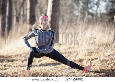 Young Fitness Woman Stretching Legs Before Jogging