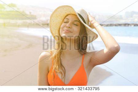 Young Cheerful Bikini Woman With Hat Enjoying Sun On Tropical Beach. Relaxing Sunbathing Holidays In