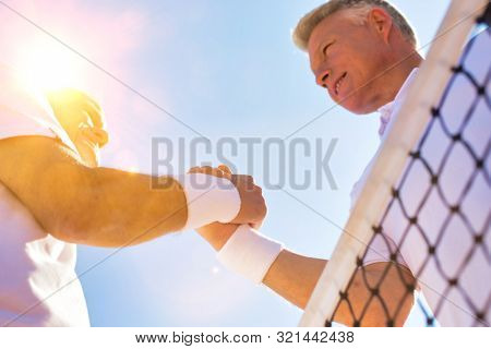 Active senior tennis players greeting each other by shaking hands with yellow lens flare in background