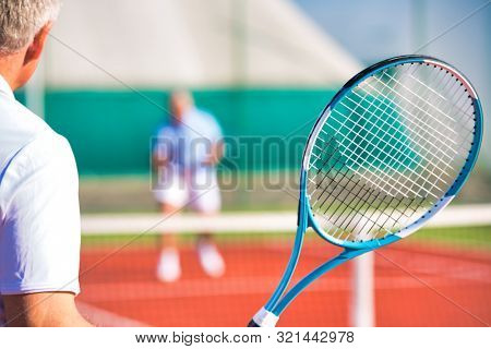 Active seniors playing tennis on sunny day at red court