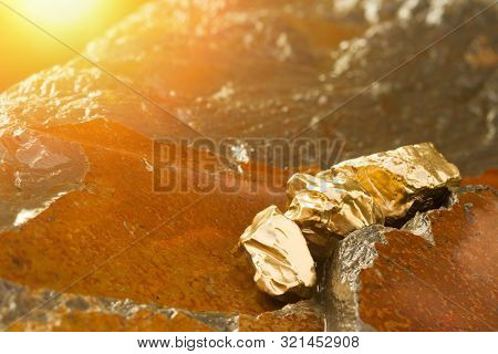 The Pure Gold Ore Found In The Mine On A Wet Stone By The River. Golden Bar In Nature With Shiny Sun
