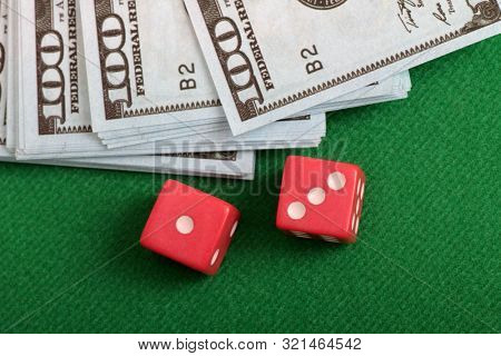 Dice and paper dollars on green cloth