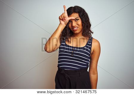 Transsexual transgender woman wearing striped t-shirt over isolated white background making fun of people with fingers on forehead doing loser gesture mocking and insulting. poster
