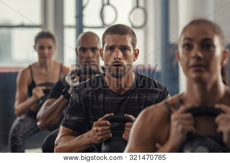 Portrait of fitness man lifting kettle bell with young women in fitness center. Active guy with group of people in gym doing weight lifting with kettlebell. Determined people in a row squatting.