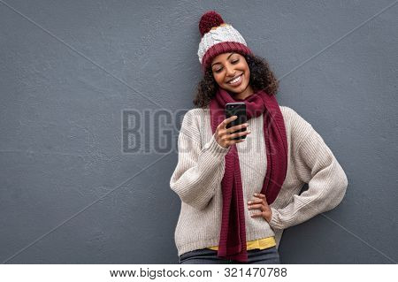 Young african woman using mobile phone standing against grey wall. Smiling black woman wearing sweater and knitted hat while surfing the net with smartphone isolated on gray background with copy space