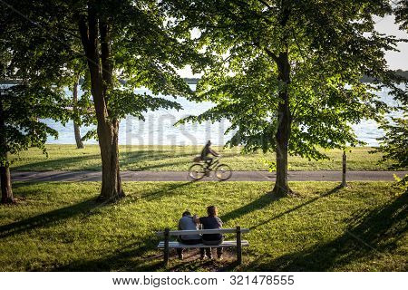 Palic, Serbia - July 1, 2018: Cyclist Passing By On The Coast Of  Palic Lake With People Sitting On