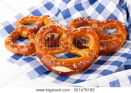 Traditional Bavarian Salty Pretzels On Blue Table Cloth, Close Up Isolated