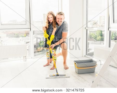 Daughter and father have fun cleaning the floor
