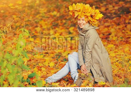 Fashion Portrait Of Young Hipster Happy Girl In Beige Coat And Ripped Jeans With Yellow Dry Fall Lea