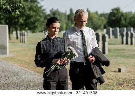 Bearded Senior Man Walking Near Woman With Flowers On Funeral