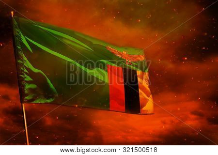 Fluttering Zambia Flag On Crimson Red Sky With Smoke Pillars Background. Zambia Problems Concept.