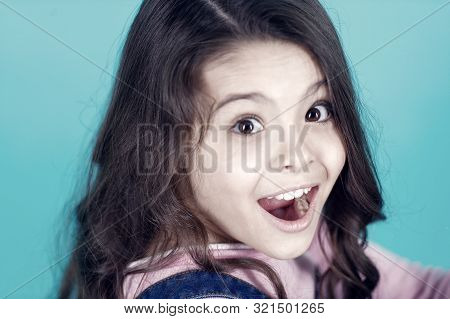 Surprised Child With Open Mouth On Blue Background. Happy Girl With Long Healthy Brunette Hair. Exce