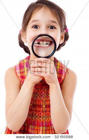 Girl showing teeth through a magnifier