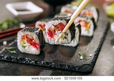Chopstock holding dragon roll with cream cheese, salmon, eel, rice, cucumber, flying fish caviar and nori. Dragon unagi maki rolls with raw red fish and tobiko on natural dark stone background closeup