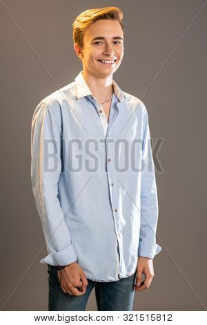 A portrait of a young goodlooking laughing guy in a white t-shirt. Beauty of men, casual fashion.