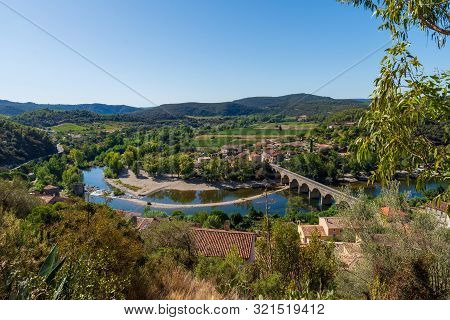 Landscape Of The Bend And Bridge On The River Orb Leading Into The Village Of  Roquebrun  In The Hau