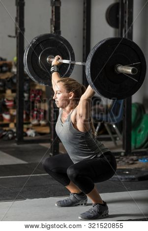 Strong female weight lifter doing snatch with heavy barbell in gym.